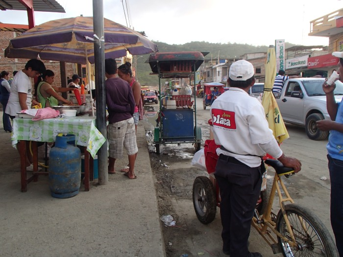 Vendors and their real estate on one corner of the main intersection.  The guy in the white sold avena, an oat drink, from a cooler on the front of his bike.  He would be in this spot from early morning until evening, every day until he sold out.